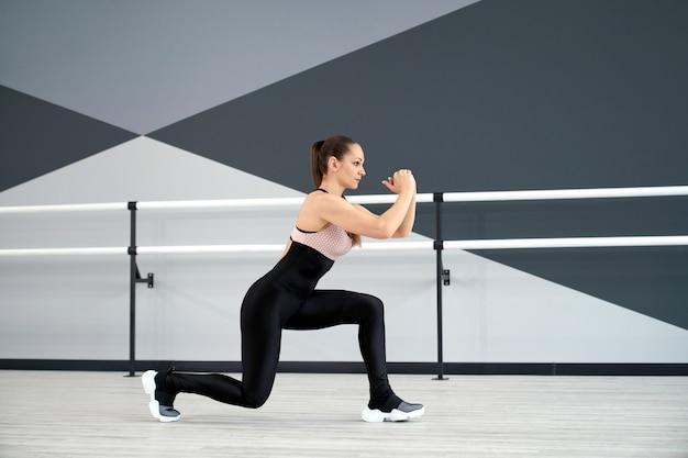 Garota treinando pernas no salão de dança