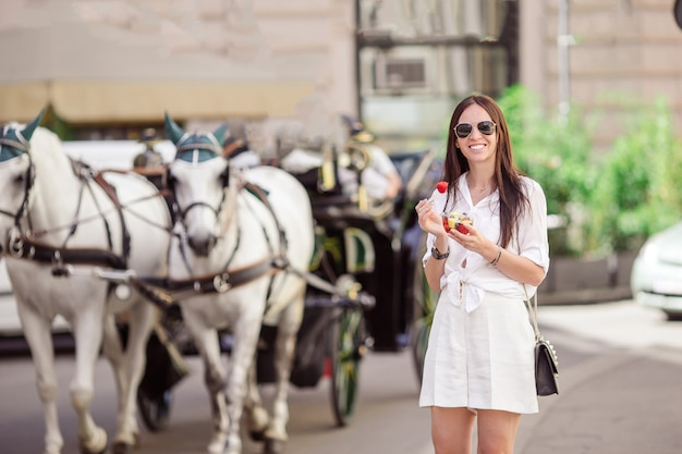 Garota turista curtindo férias em viena e olhando para os belos cavalos na carruagem