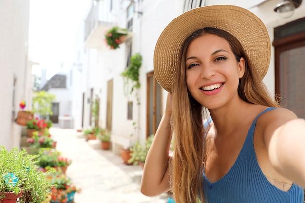 Garota turista tirando autorretrato em uma vila aconchegante do sul da europa