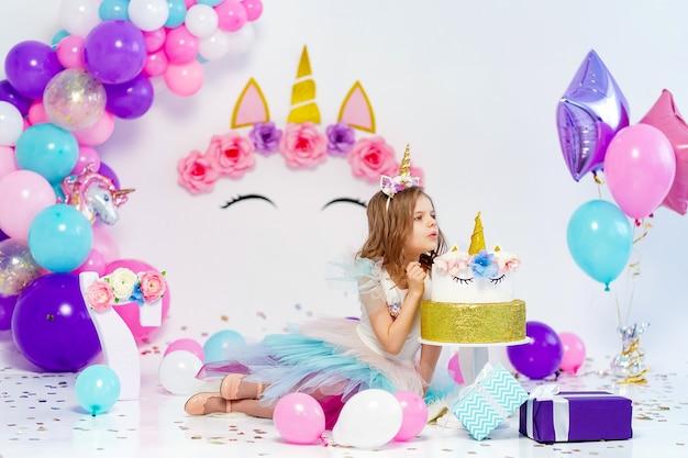 Garota unicórnio posando perto de uma ideia de bolo de feliz aniversário para decoração
