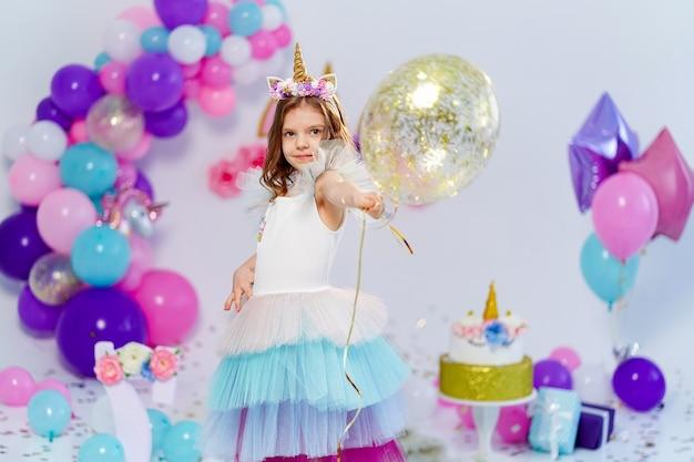 Garota unicórnio segurando uma ideia de balão de ar de confete dourado para decoração