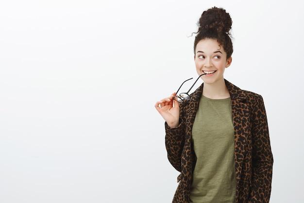Garota urbana criativa sonhadora com casaco de leopardo, mordendo a borda dos óculos e olhando bem com um sorriso curioso, pensando ou tendo alguma ideia curiosa