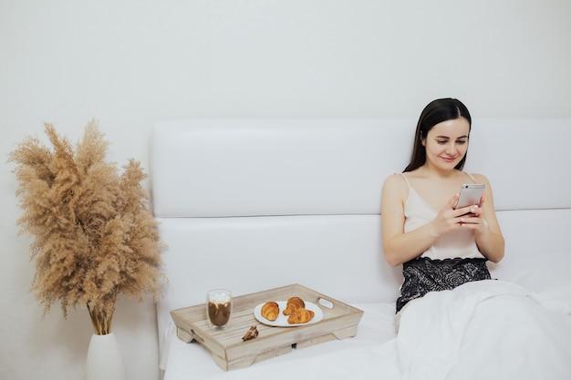 Garota usa seu smartphone durante o café da manhã na cama em casa