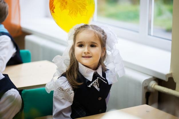 Garota usa um uniforme escolar na escola