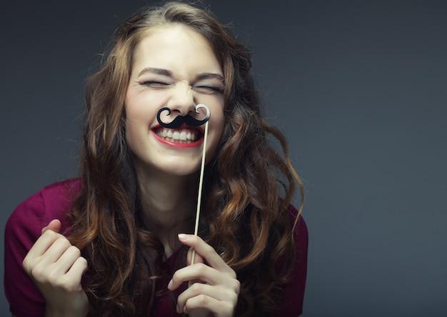 Garota usando bigodes falsos.