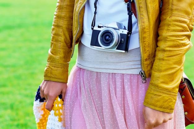 Garota usando uma câmera antiga na alça de pescoço.