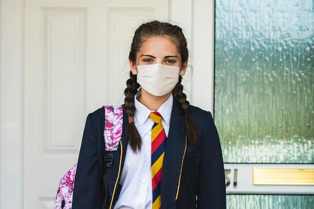 Garota usando uma máscara e indo para a escola no novo normal