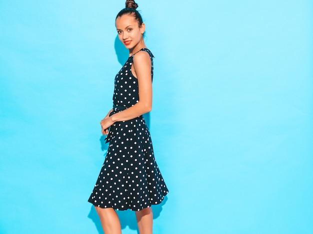 Garota usando vestido de bolinhas. levantamento modelo perto da parede azul no estúdio. fêmea positiva