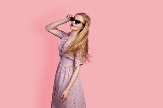Garota usando vestido e óculos escuros posando, girando em torno de si mesma sobre um fundo rosa no estúdio