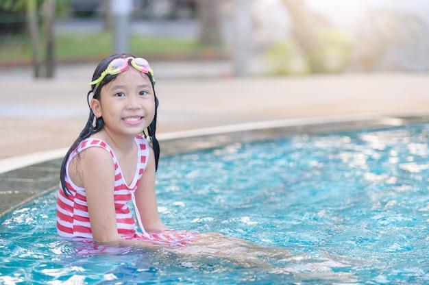 Garota usar óculos de proteção e sorrir na piscina