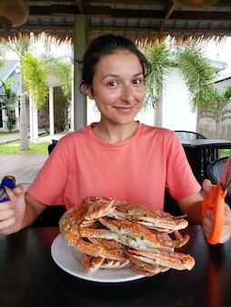 Garota vai comer caranguejos cozidos. garota na mesa com um prato cheio de caranguejos azuis cozidos.