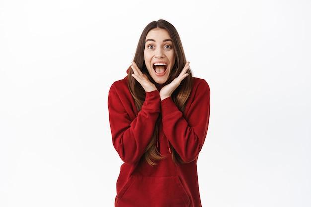 Garota vencedora animada grita de surpresa legal e alegre, boca aberta fascinada, olhando impressionada e feliz na frente, comemorando, em pé sobre uma parede branca