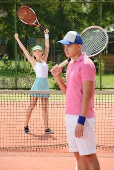 Garota venceu o cara no tênis levantou as mãos e se alegra.