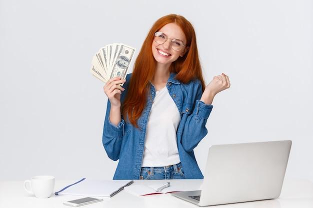 Garota vendeu seu programa, freelancer foi pago pelo projeto, design branco alegre, punhos trêmulos triunfando, comemorando muito dinheiro, ganhou o prêmio, segurando dólares em dinheiro