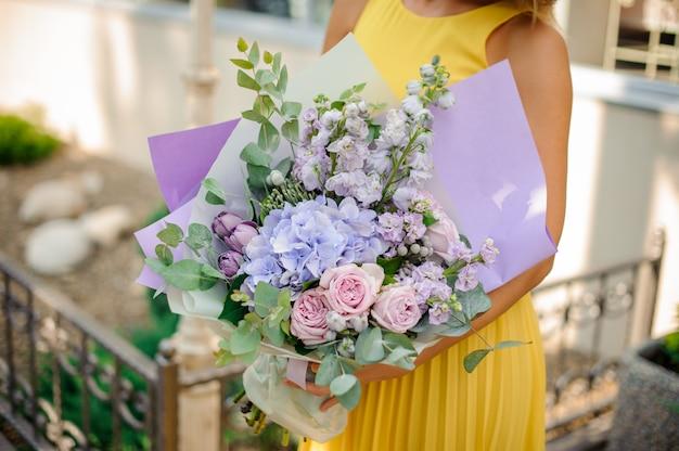 Garota vestida com um vestido amarelo, segurando um buquê roxo de flores