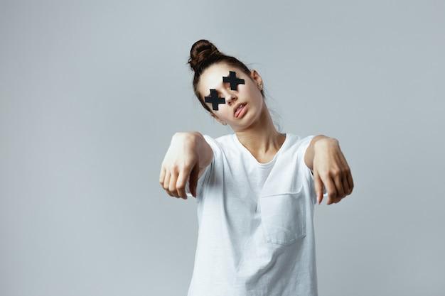 Garota vestida com uma camiseta branca com cruzes pretas de fita adesiva nos olhos está posando como um zumbi no fundo branco no estúdio.