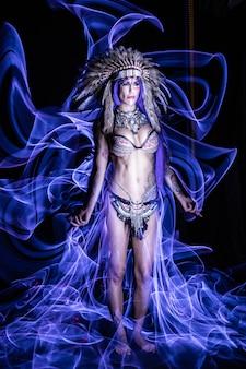 Garota vestida como um índio com penas na cabeça posa no escuro para fotografia de lightpainting.