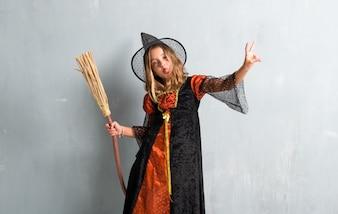 Garota vestida como uma bruxa e segurando uma vassoura para as férias de halloween, fazendo o gesto de vitória