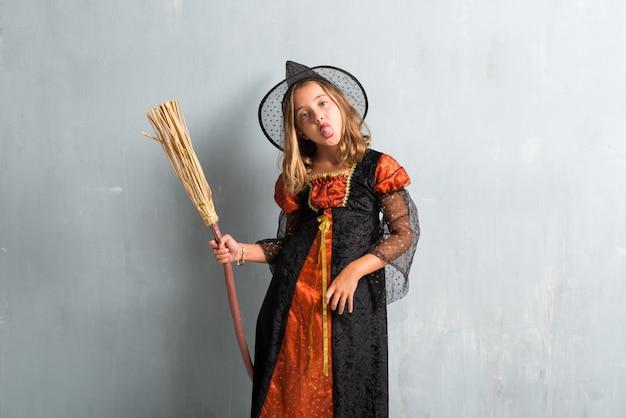 Garota vestida como uma bruxa e segurando uma vassoura para as férias de halloween tirando a língua