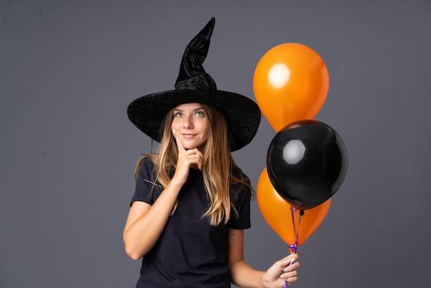 Garota vestida como uma bruxa para o halloween e tendo dúvidas