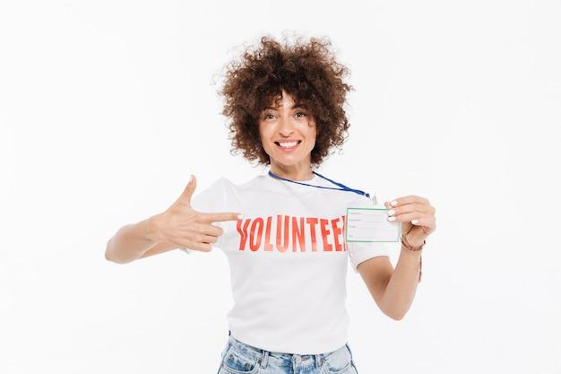 Garota vestida de camiseta voluntária, apontando o dedo para seu crachá