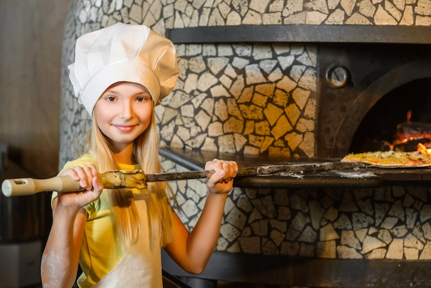 Garota vestida de cozinheira preparando pizza