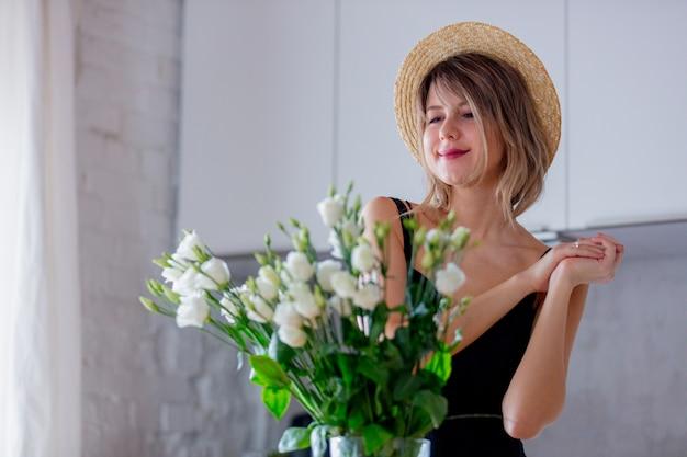 Garota vestida em um vestido preto perto de buquê de rosas brancas em um vaso