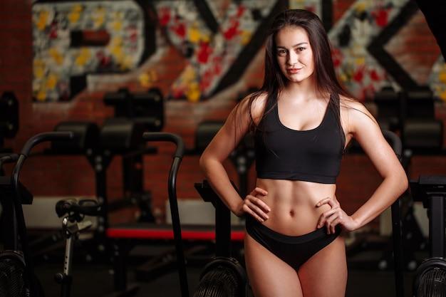 Garota vestindo blusa preta e calça posando no ginásio