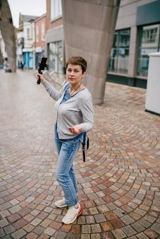 Garota vestindo casaco de lã cinza, segurando a vara de selfie, tirando fotos e andando pela cidade