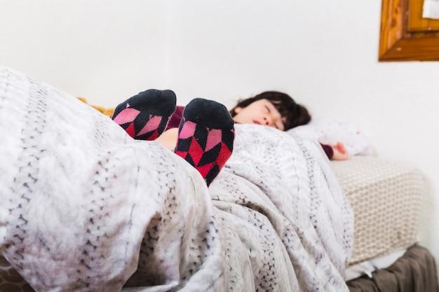 Garota vestindo meias coloridas enquanto cochilava na cama