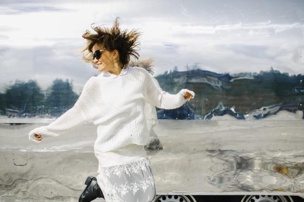 Garota vestindo roupas brancas salta ao lado do veículo cintilante