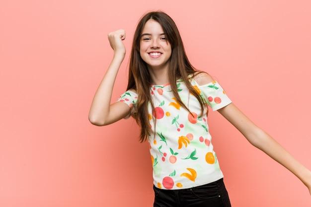 Garota vestindo roupas de verão contra uma parede dançando e se divertindo.