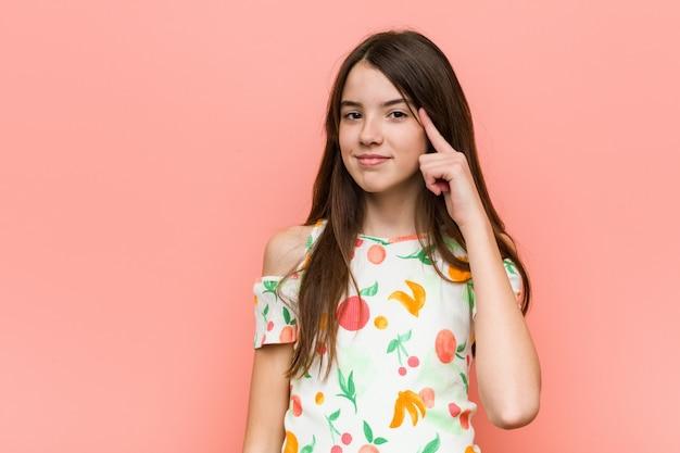 Garota vestindo roupas de verão contra uma parede rosa, apontando a cabeça com um dedo