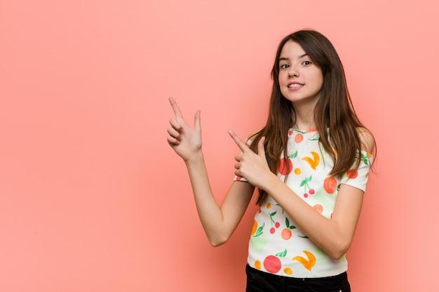 Garota vestindo roupas de verão contra uma parede rosa chocado apontando com os dedos indicadores