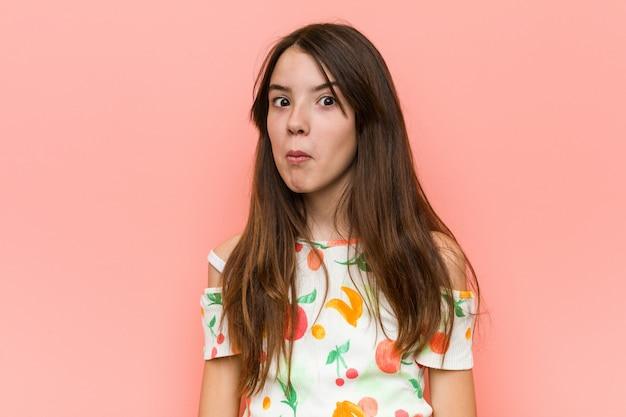 Garota vestindo roupas de verão contra uma parede vermelha encolhe os ombros e abre os olhos confusos.