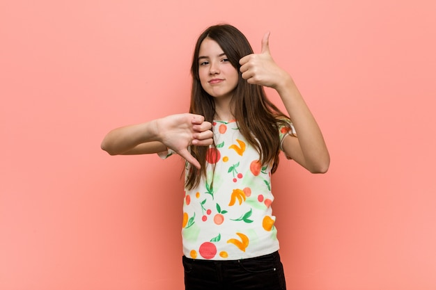 Garota vestindo roupas de verão contra uma parede vermelha, mostrando os polegares para cima e os polegares para baixo, difícil escolher