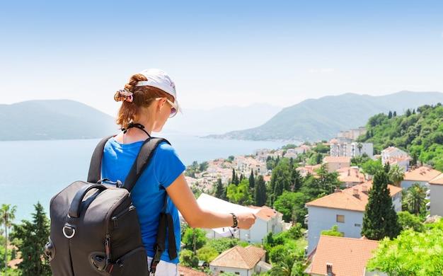 Garota viajando com mapa e mochila lendo um mapa