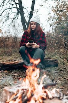 Garota viajante com camisa xadrez e chapéu usa um smartphone