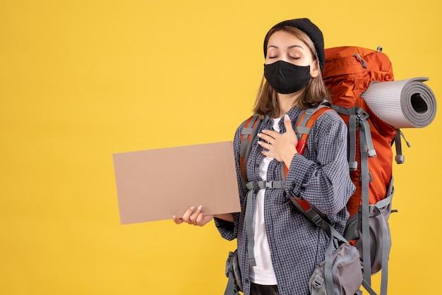 Garota viajante com máscara preta e mochila colocando a mão no peito segurando papelão