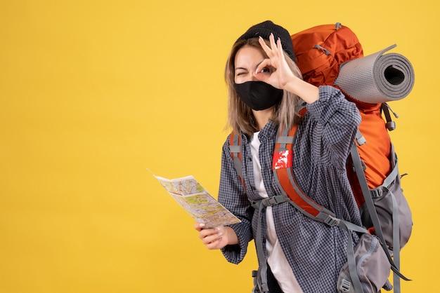 Garota viajante com máscara preta e mochila segurando o mapa, colocando a placa de ok na frente do olho