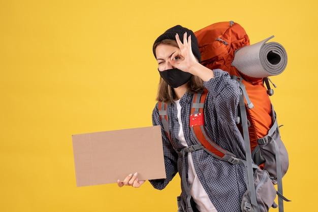 Garota viajante com máscara preta e mochila segurando um papelão, colocando a placa de ok na frente do olho