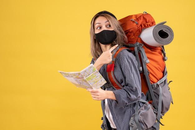 Garota viajante com máscara preta segurando um mapa apontando para a mochila