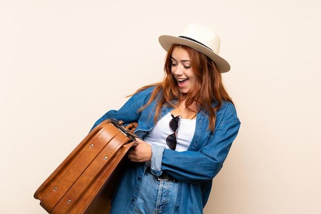 Garota viajante ruiva com mala com expressão feliz