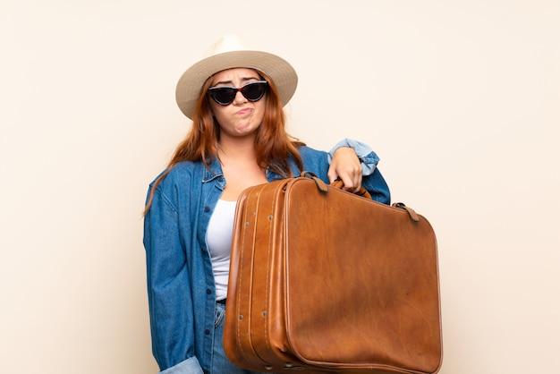 Garota viajante ruiva com mala com expressão triste
