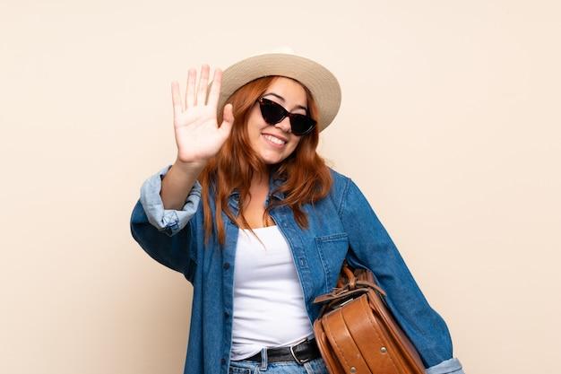 Garota viajante ruiva com mala saudando com mão com expressão feliz