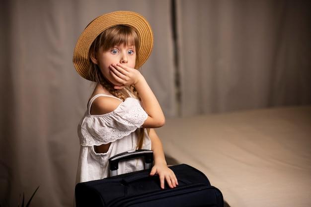 Garota viajante surpresa com uma mala de viagem na mão e usando um chapéu em estado de choque em confusão cobre a boca com a mão surpresa no quarto do hotel
