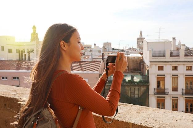 Garota viajante tirando foto do terraço da paisagem urbana de valência, espanha