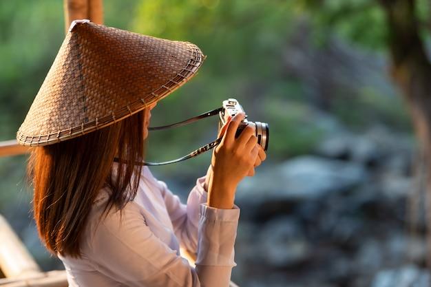 Garota vietnamita em traje tradicional, segurando uma câmera de filme no meio da natureza