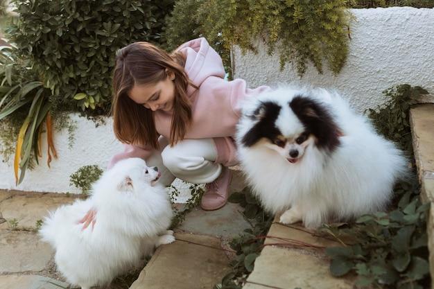 Garota vista lateral e cachorros brincando na escada