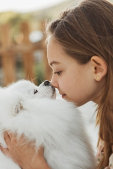 Garota vista lateral tocando o nariz do cachorro